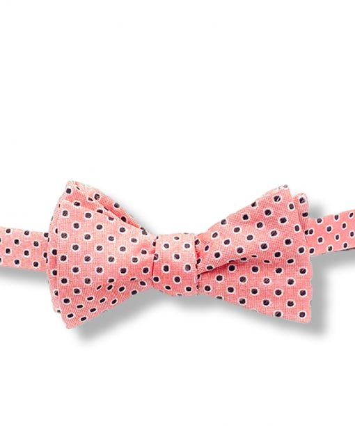 A pink polka dot self bow tie that looks like a king salmon pattern