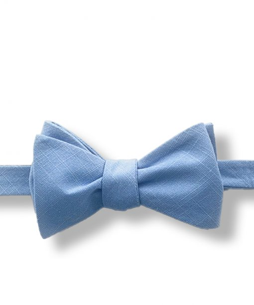 a light blue solid color cotton bow tie that is self tie and shown tied