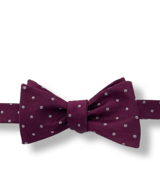 maroon polka dot silk bow tie that is self tie and shown tied