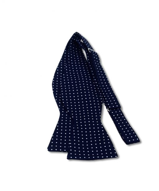 navy blue mini polka dot bow tie that is self tie and shown untied