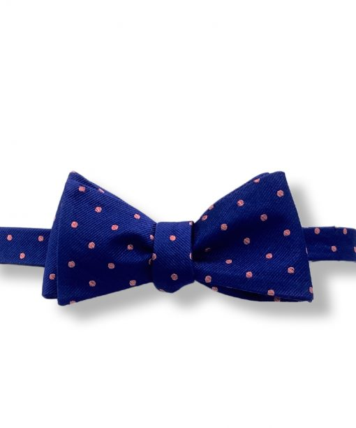 navy blue and pink polka dot silk bow tie that is self tie and shown tied