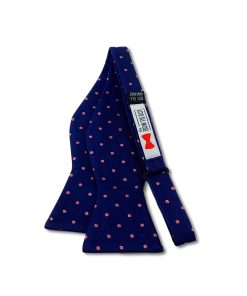 navy blue and pink polka dot silk bow tie that is self tie and shown untied
