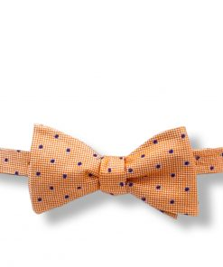 orange and navy polka dot silk bow tie that is self tie and shown tied