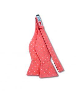 a pink bow tie with white polka dots silk material self tie and shown untied