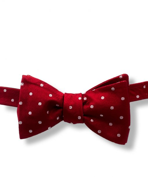 red and white polka dot silk self tie bow tie that is shown tied